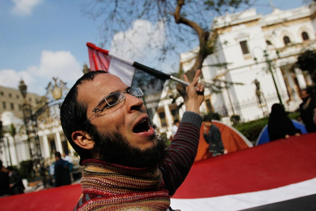 An anti-government protester shouts in front of the Egyptian Parliament building as protests against the Government entered a 16th day.