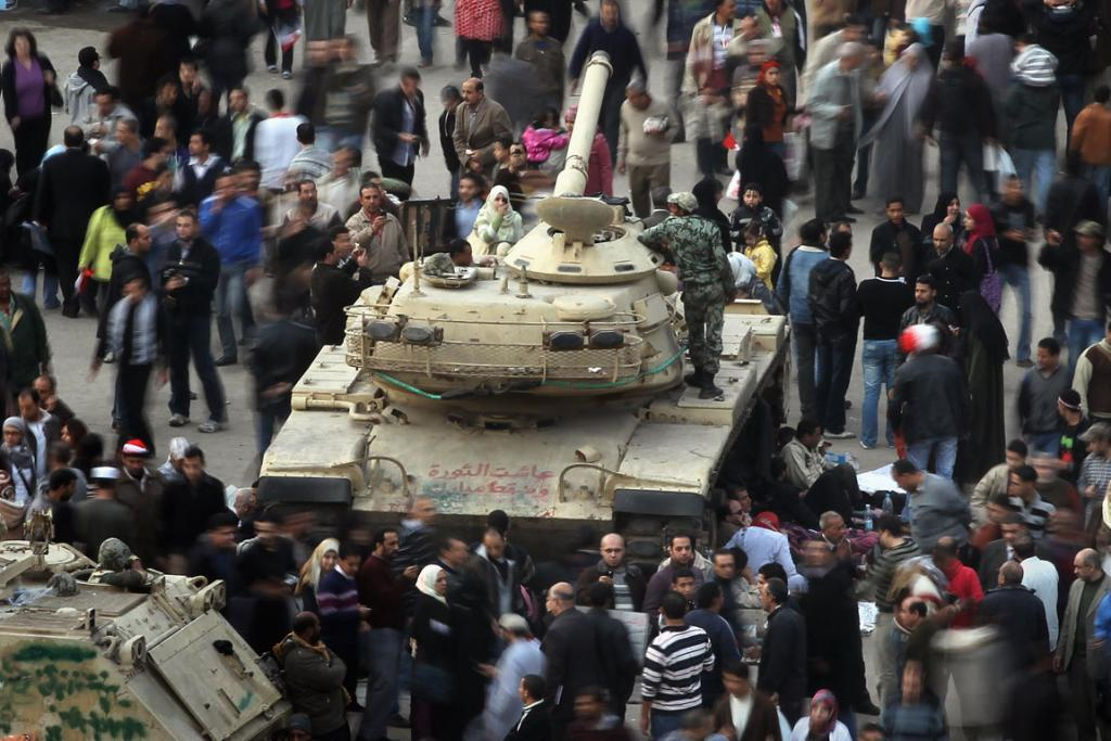 Anti-government protesters mill around an Egyptian army tank in Tahrir Square. More than two weeks into Egypt's uprising, demonstrators continue to occupy the square, demanding the resignation of President Hosni Mubarak.