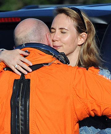 A 2008 file photo shows Gabrielle Gifford hugging her husband, Shuttle Discovery Commander Mark Kelly, at Kennedy Space Center.