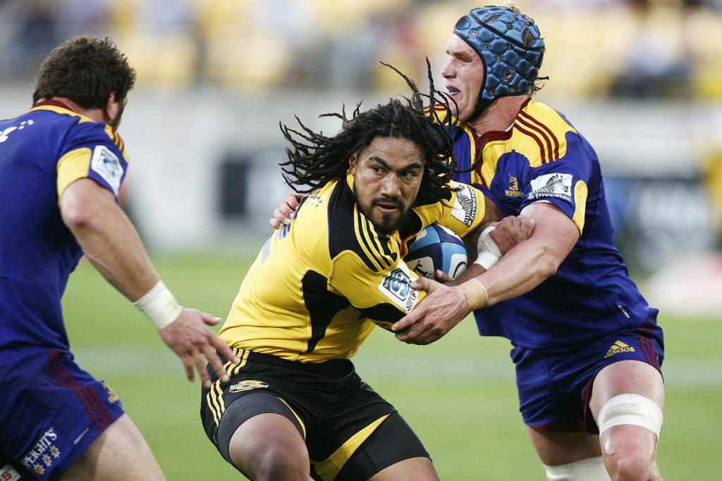 Hurricanes second-five Ma'a Nonu, who received a red card, tries to break out of Josh Bekhuis' tackle.