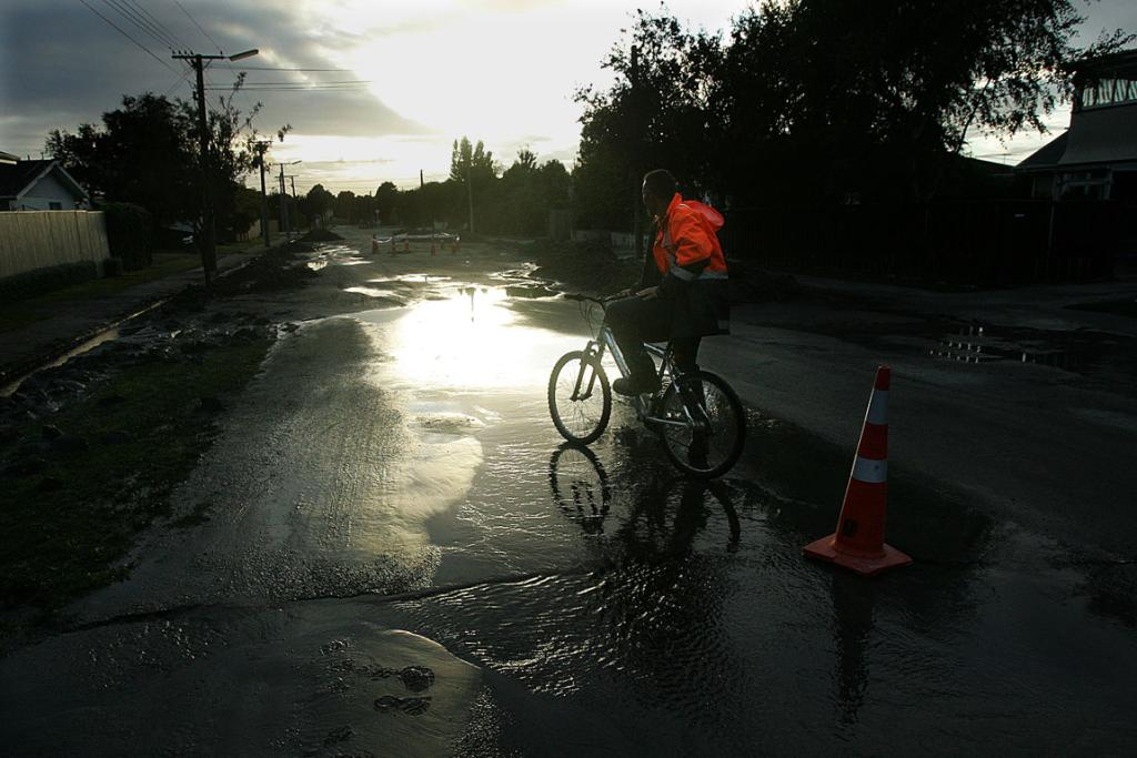 A cyclist rides through a silt and water logged street in the suburb of Richmond.