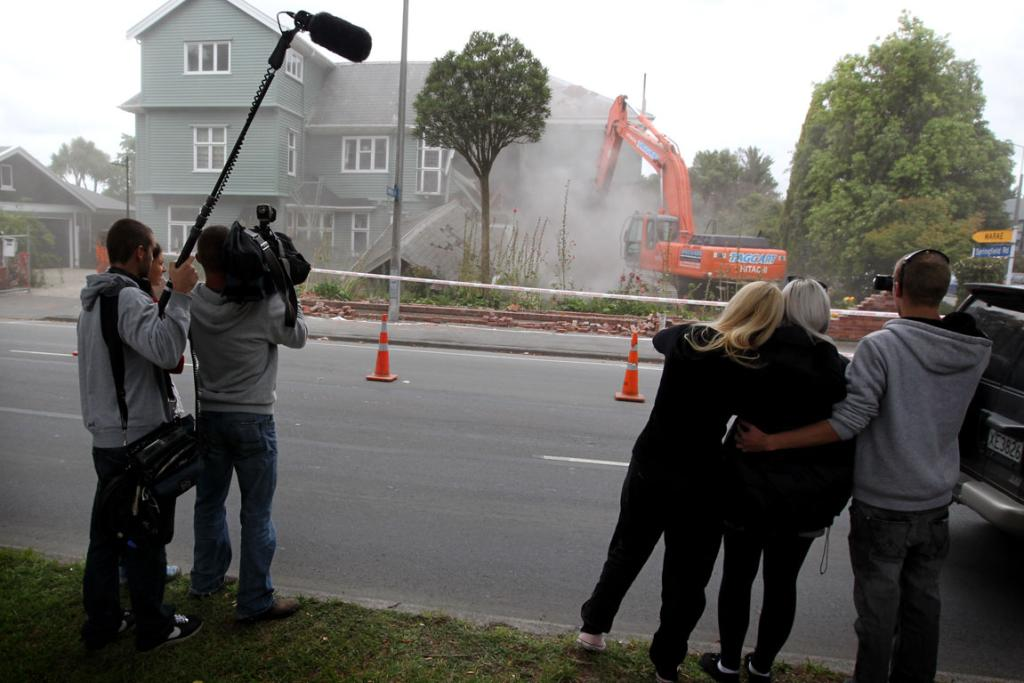 Members of the Smith family watch as their historic house is demolished in Christchurch. The 1850s-era Hambledon Bed and Breakfast was left uninhabitable after the September quake.