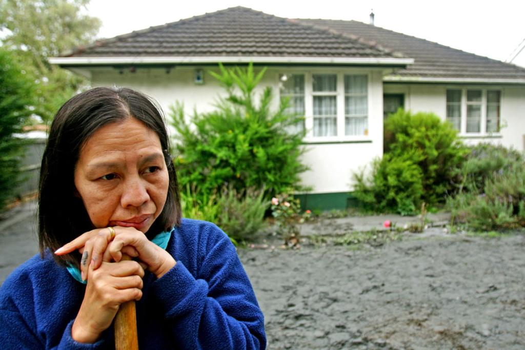 Shirley resident Noy Godfrey doesn't know where to start as she cleans the sand from the front of her home.