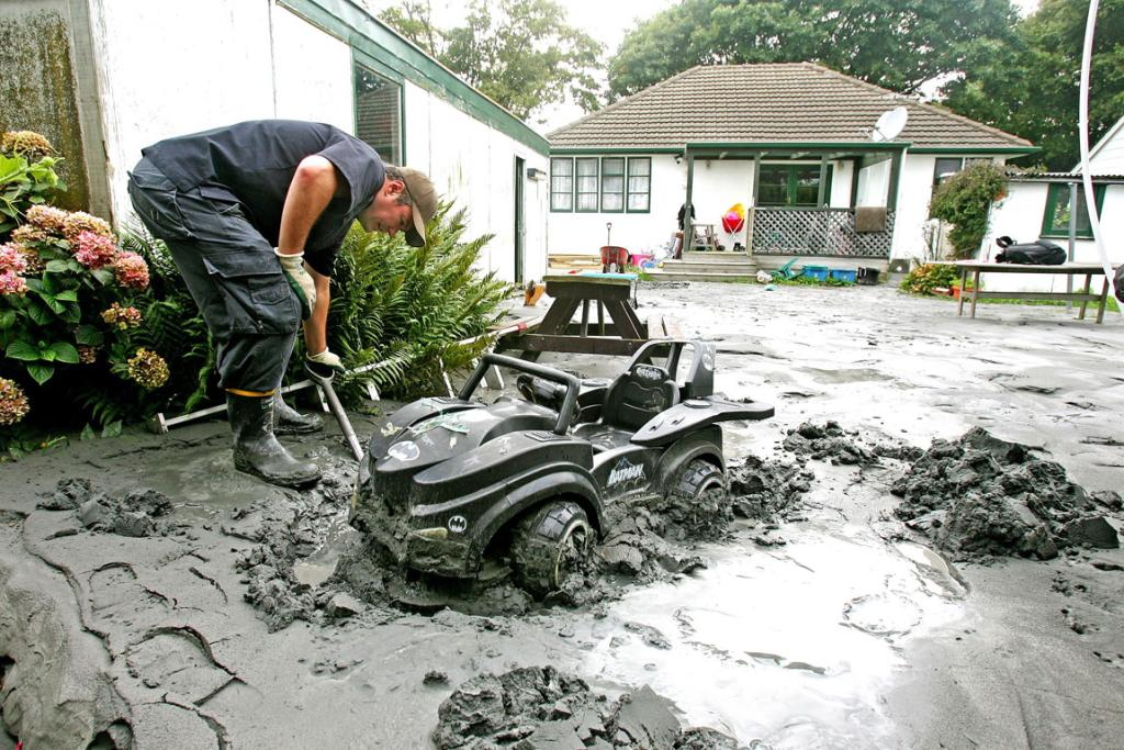 Shirley resident Paul Stratford cleans the sand away from his daughter's toy Batmobile.
