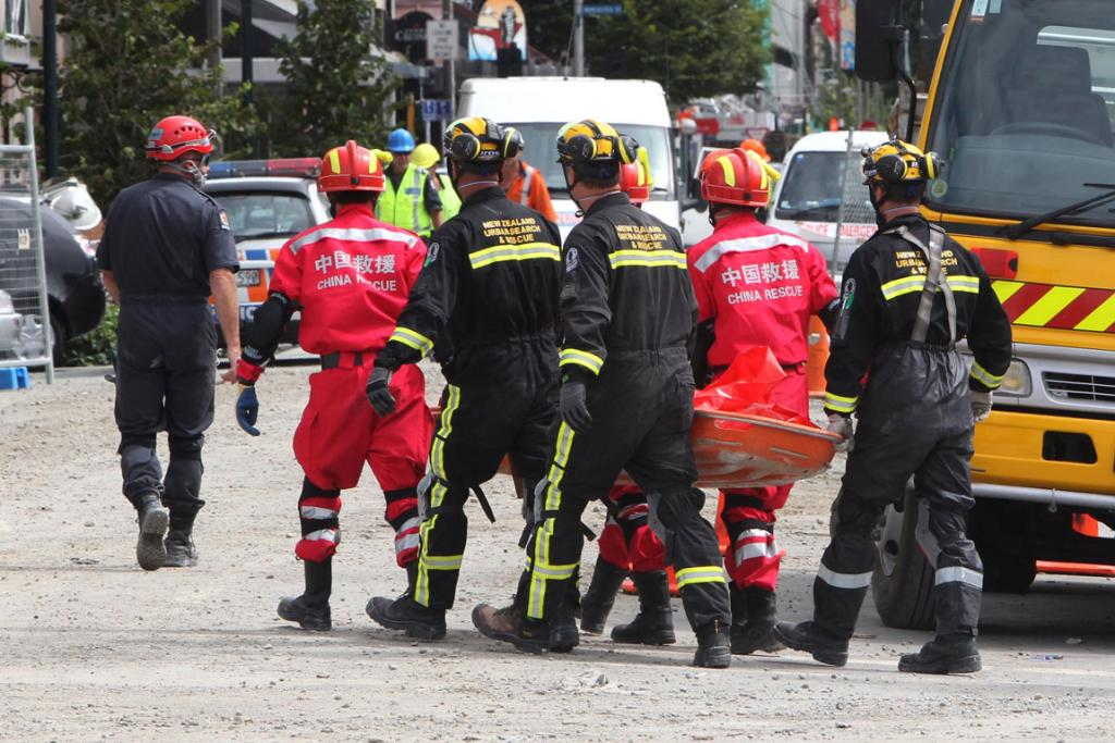 A Chinese recovery team works with members of New Zealand Urban Search and Rescue to carry a body from the Canterbury TV site.