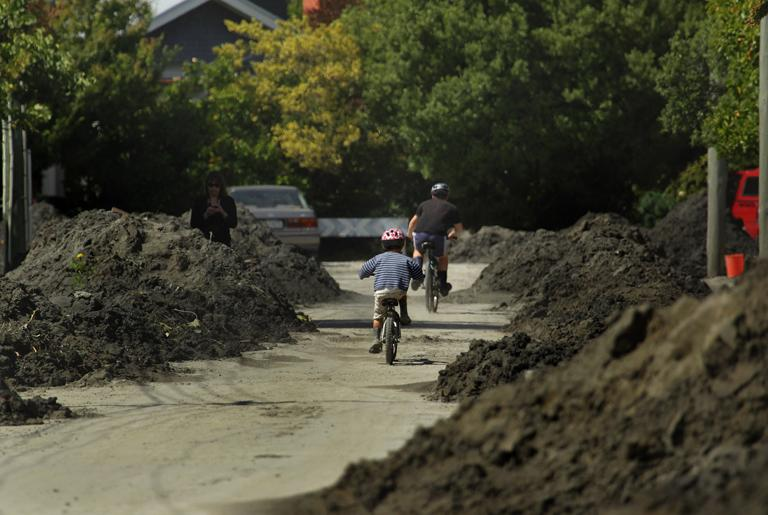 Children ride their bikes past huge piles of liquefaction along Roxburgh street in Beckenham. Farmers spent the morning clearing the silt and making the road passable.