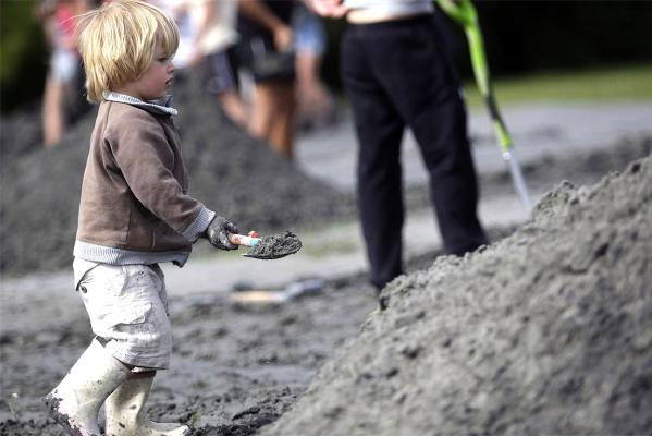 Zack Fastier, 3, lends a hand in the clean-up effort following the quake.