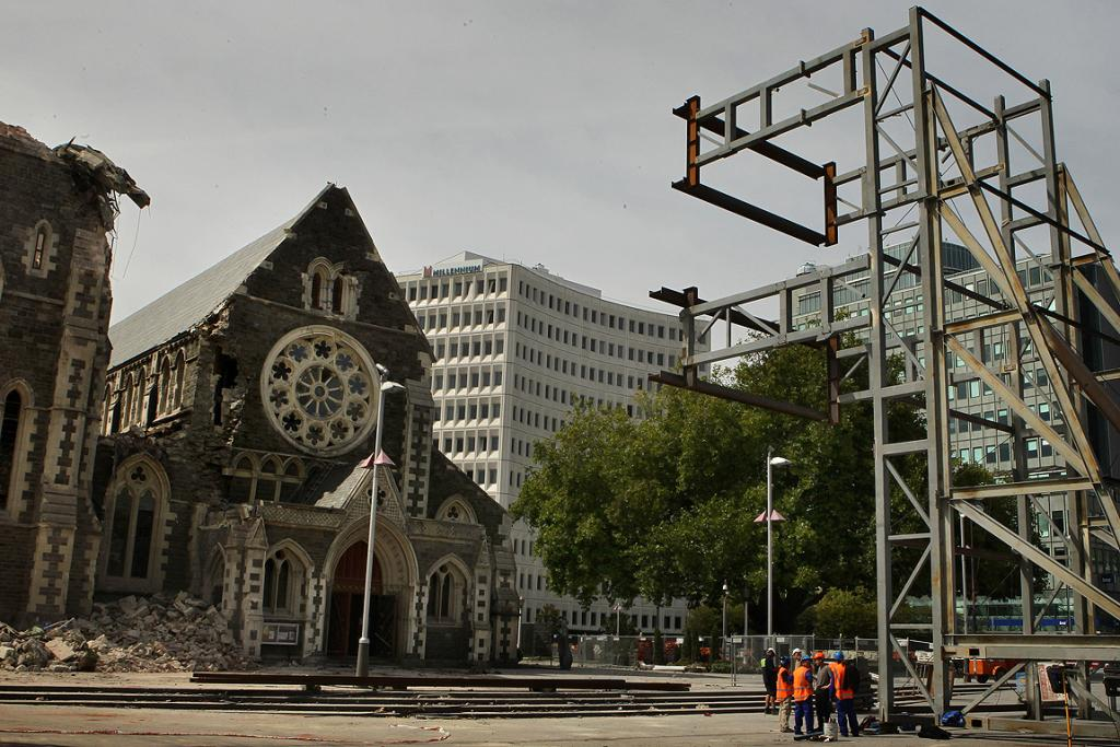 Emergency workers stand near the frame that will be used to hold the facade of the Christchurch Cathedral in place.