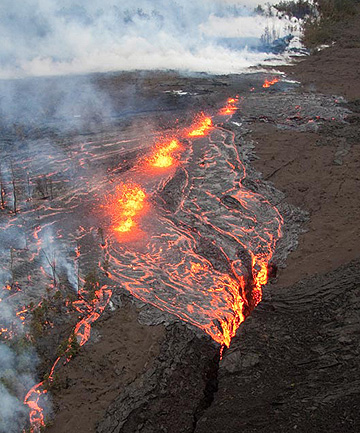 LAVA FLOW: Lava pours from the fissure just after daybreak and cascades out of into a deep crack near at the Kilauea volcano on Saturday.