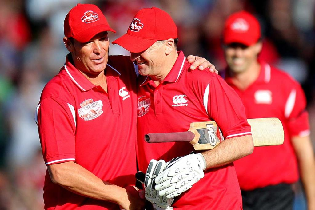 Australian cricket great Shane Warne congratulates New Zealand PM John Key after his over in the middle.