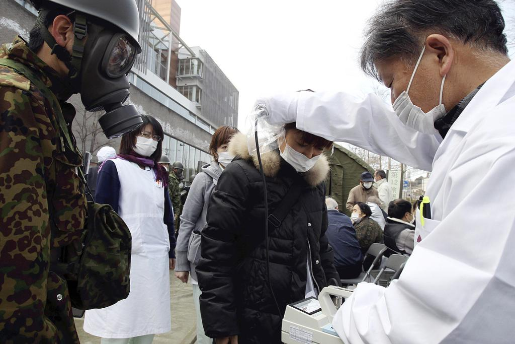 A doctor checks uses a giger counter to check the level of radiation on a woman while a soldier in gas mask looks on at a radiation treatment centre in Nihonmatsu city in Fukushima prefecture.