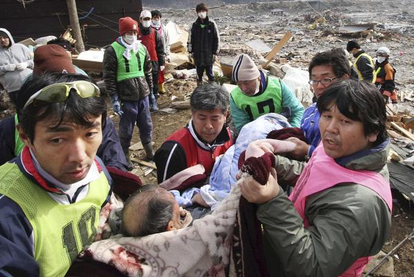 Rescue workers carry an elderly man found alive under rubble along a slope of a hill in Minamisanriku in Miyagi Prefecture.