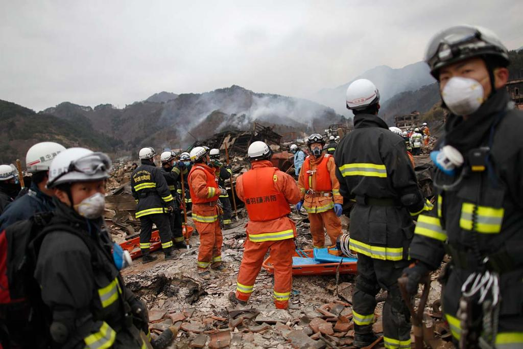 Rescue workers arrive at the devastated residential area of Otsuchi, where an entire village was wiped out, as the forest burns above the town March 15, 2011.