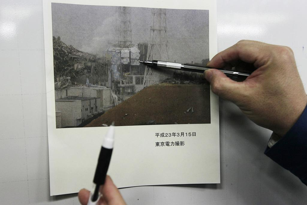 Tokyo Electric Co. employees in charge of public relations use a photo of the Fukushima Daiichi nuclear complex to explain the situation during a press conference.