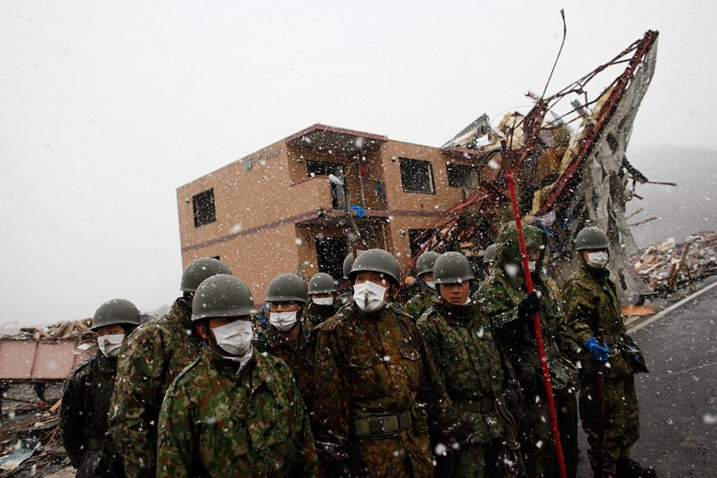 Members of the Japan Self-Defense Force listen arrive at the devastated residential area in Otsuchi as heavy snow falls March 16.
