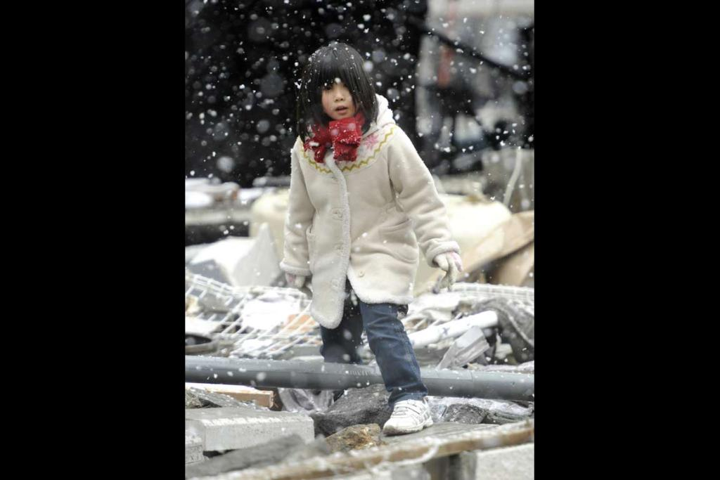 A girl searches through the rubble near her home in Kamashi.