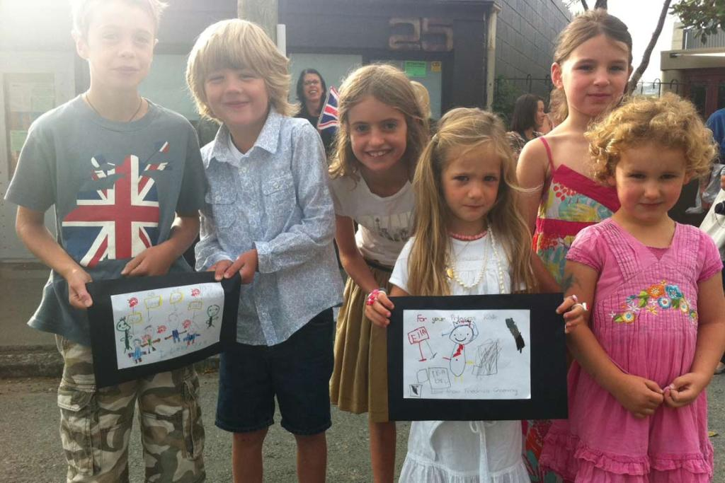 Children waiting to see Prince William with pictures they have drawn for him.