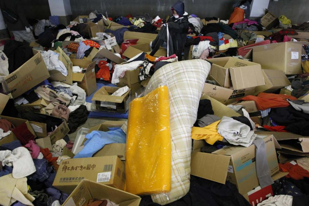 A boy searches for clothes among items donated by people at a Red Cross office in Otsuchi, Iwate Prefecture in northern Japan.
