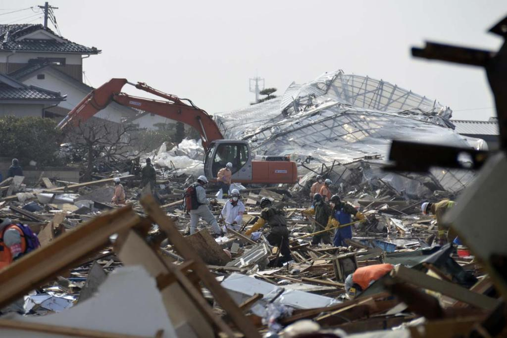 Workers and rescuers amid debris of buildings wrecked by last week's earthquake and tsunami in Natori City, Miyagi Prefecture, northeastern Japan.