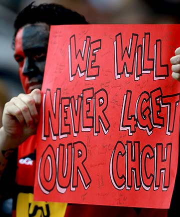 A fan displays a banner in memory of the Christchurch earthquake  ahead of the round six Super Rugby match between the Crusaders and the Sharks at Twickenham in London.