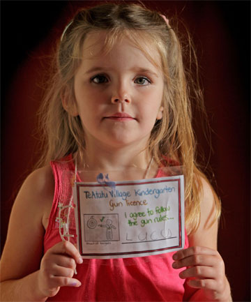 "SAFETY FIRST: Lucy Coup, 4, shows off the laminated gun licence she earned for learning the dangers of and rules about using guns. ""We don't shoot people, because it might hurt them,'' she says."