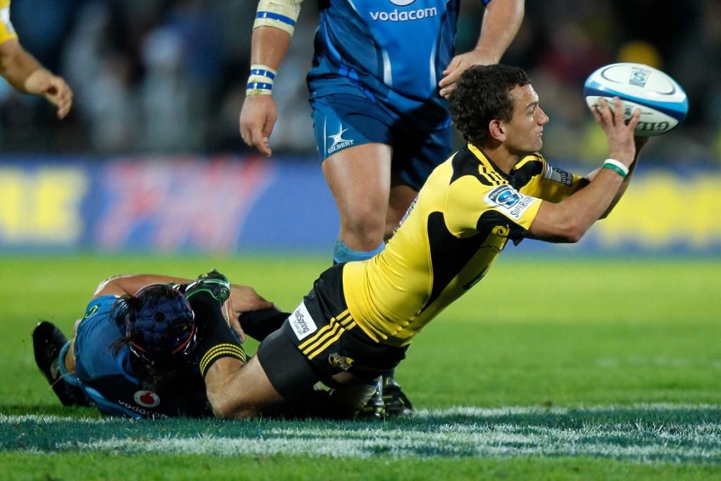Aaron Cruden of the Hurricanes is tackled by Victor Matfield.