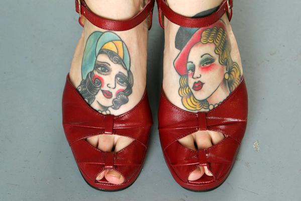 A visitor displays her tattooed feet as she walks around a 2005 international tattoo exhibition in east London.
