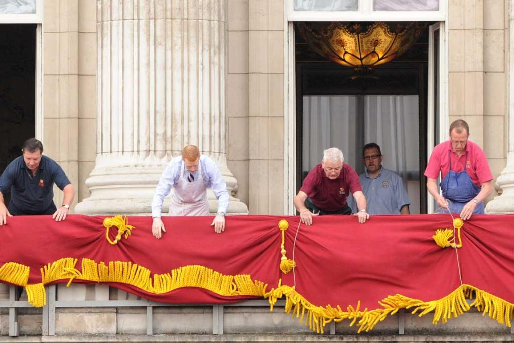 Workers make the final preparations on the balcony of Buckingham Palace.