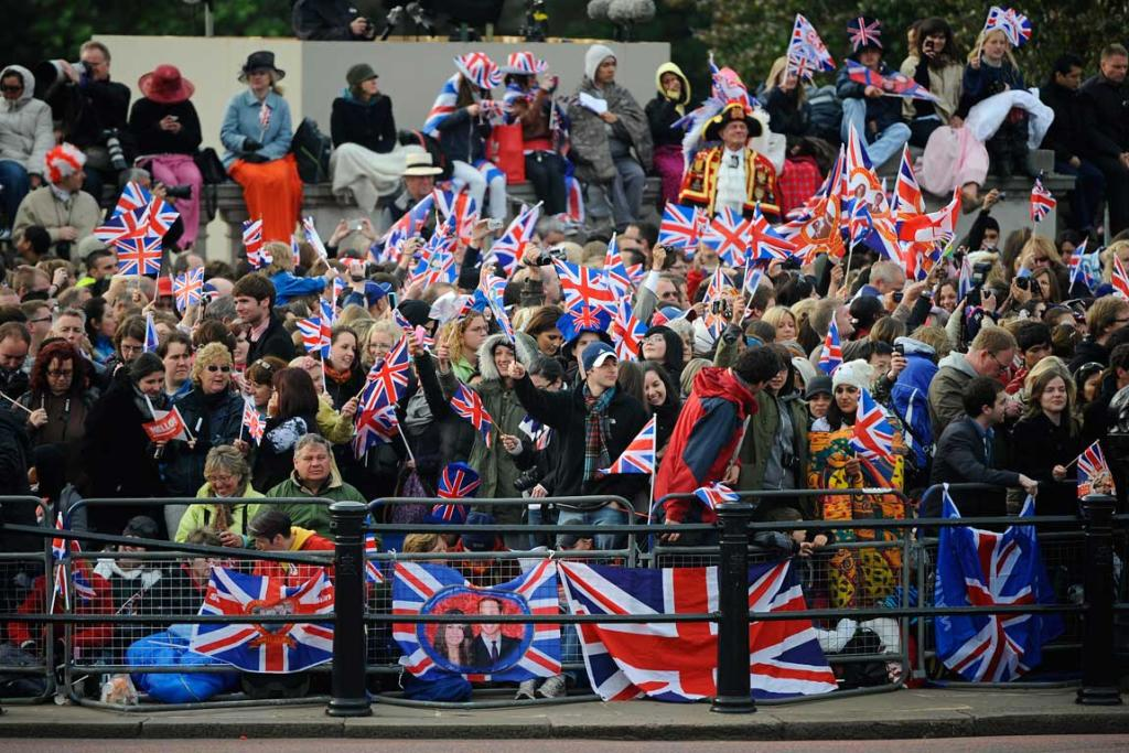 Royal supporters wave British Union Jack flags along the processional route.