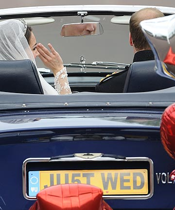 Prince William and Princess Kate leave Buckingham Palace after their wedding reception driving an Aston Martin with the number plate JU5T WED.