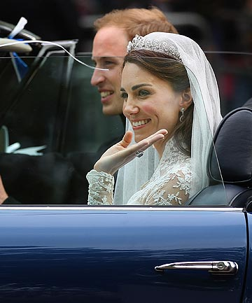 Princess Kate waves as husband Prince William drives an Aston Martin away from Buckingham Palace after their wedding reception.