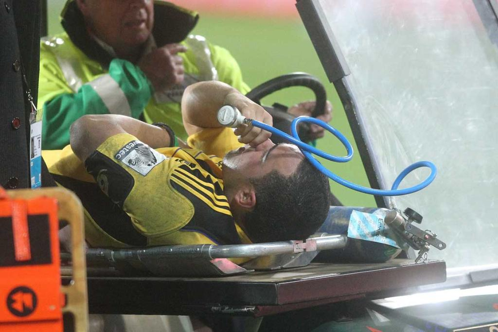 Charlie Ngatai of the Hurricanes leaves on a stretcher against the Reds.