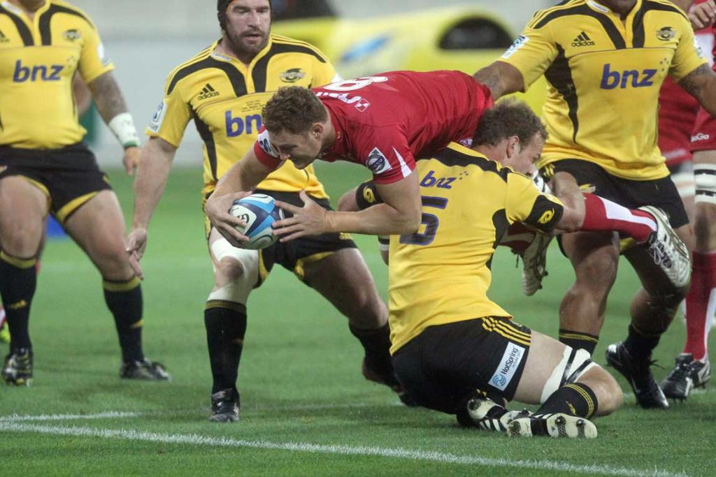 Scott Higginbotham of the Reds scores a try against the Hurricanes.