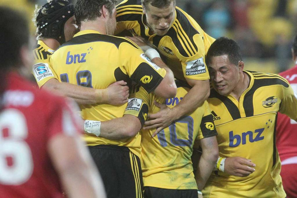 Aaron Cruden is swamped by his Hurricanes teammates after kicking the winning goal against the Reds.