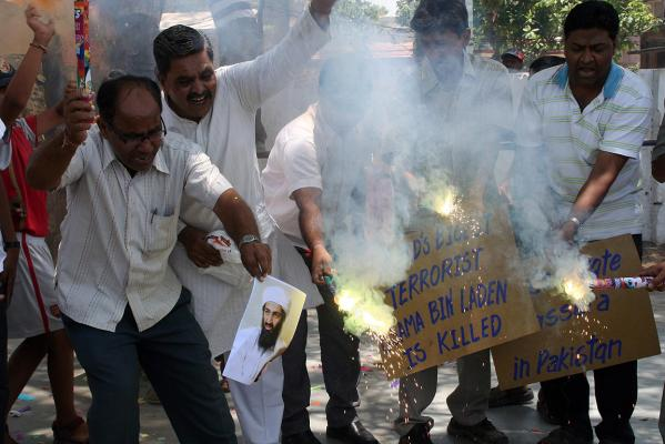 People burn a photograph of al Qaeda leader Osama bin Laden as they celebrate his death, in the western Indian city of Ahmedabad.