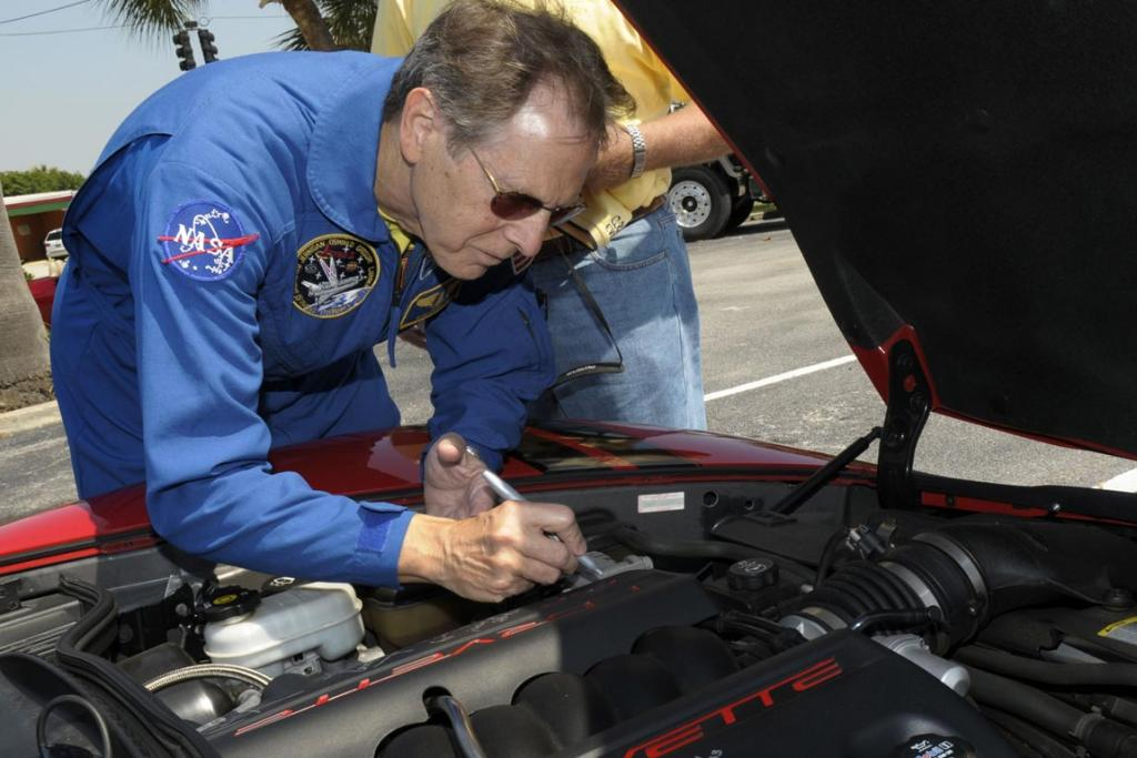 SIGN HERE: Astronaut Sam Durrance autographs the engine block of 2006 Corvette owner Jack Legere, of Titusville, Florida after a parade commemorating the historic flight of Alan Shepard, the first American to travel into outer space in Cocoa Beach, Florida.