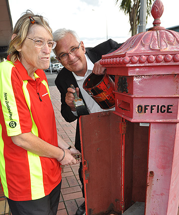 BOXING ON: NZ Post Hawera postie Mia Aarts and South Taranaki District Council's John Sargeant with the Penfold hexagonal letterbox that is being retired.