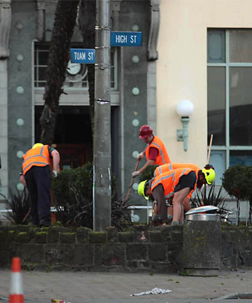 WEEDING: Christchurch's City Care workers tend a garden outside Alice in Videoland in High St, inside the red zone.
