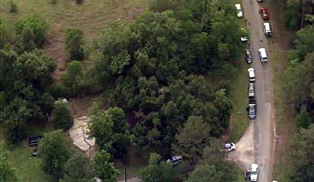 An image provided by KPRC-TV shows authorities at a rural house after receiving a tip that multiple dismembered bodies are buried there, in Liberty County, Texas.