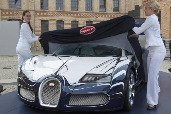 Two women unveil a unique version of a Bugatti Veyron Grand Sport L'Or Blance in Berlin.
