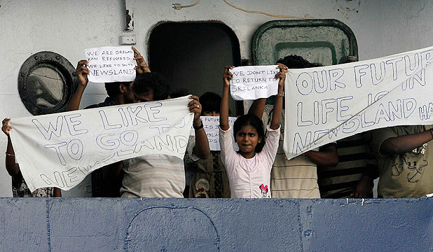 'WE NEED NEW ZEALAND': Asylum seekers from Sri Lanka on a ship in Bintan island hold up signs saying they want to go to New Zealand.