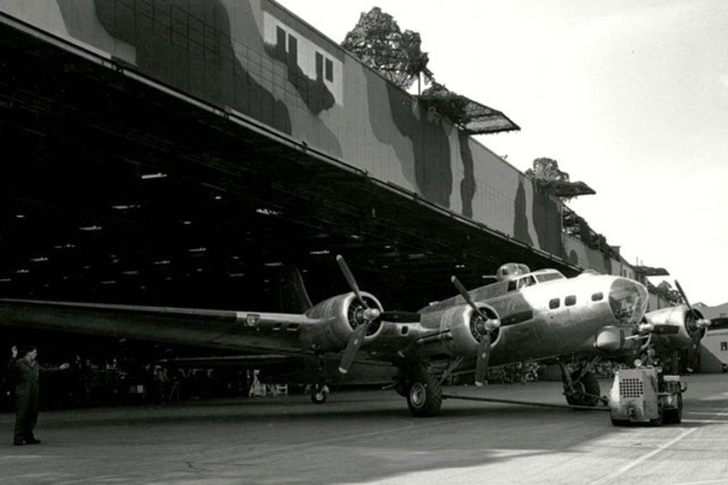 SNEAKY: Boeing Plant 2 in 1944. B-17G Flying Fortress. Fake trees and camouflage paint can be seen above the plane.