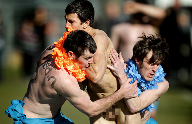 ON-FIELD ACTION: Two Feejee Experience players tackle a Bottom Bus player during the traditional nude rugby game at Dunedin's Logan Park today.