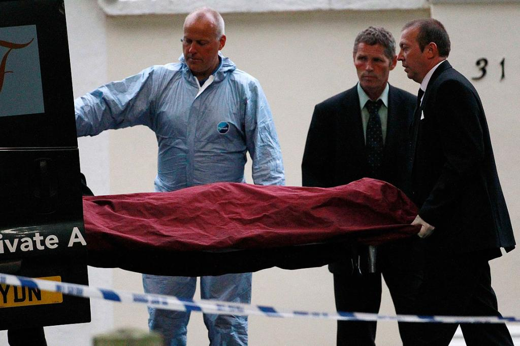 SAD MOMENT: Funeral workers carry the body of Amy Winehouse outside her house in London.