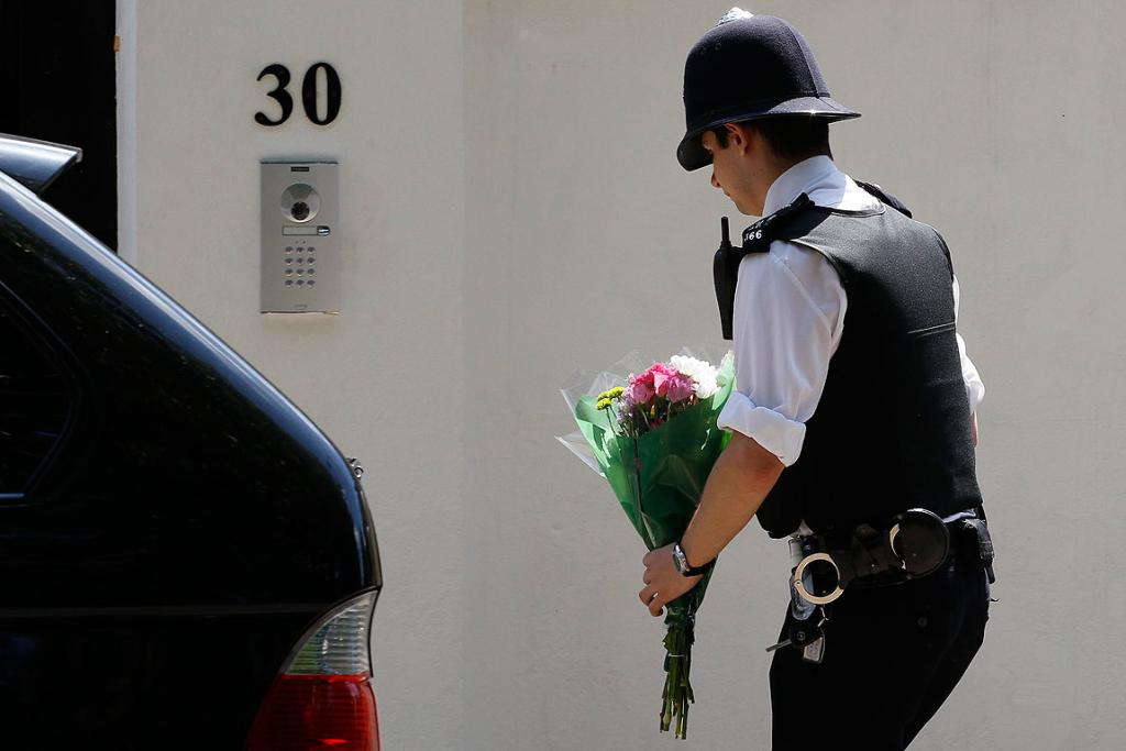 PAYING RESPECTS: A police officer places flowers outside the home of Amy Winehouse.