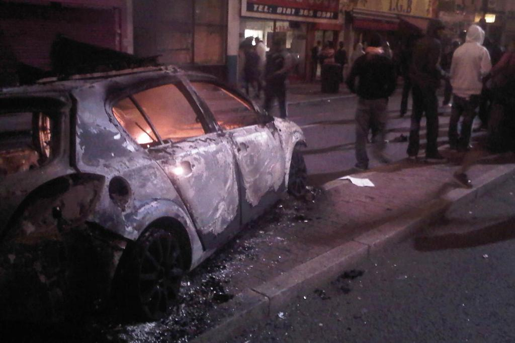 WRITE OFF: A car is burnt following riots in Tottenham, north London.
