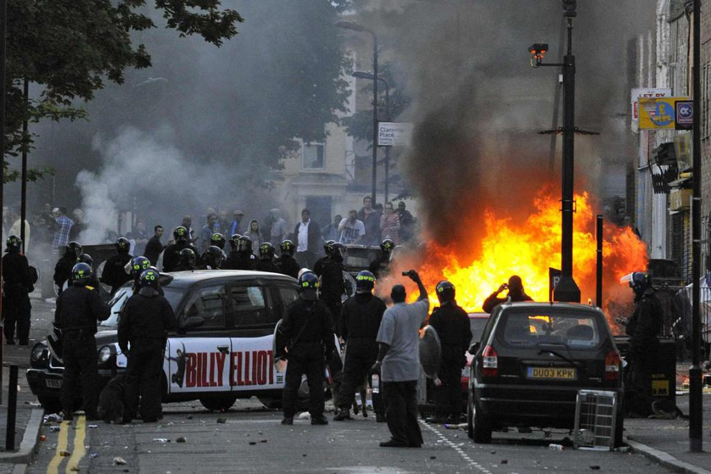 Police officers in riot gear block a road near a burning car on a street in Hackney.