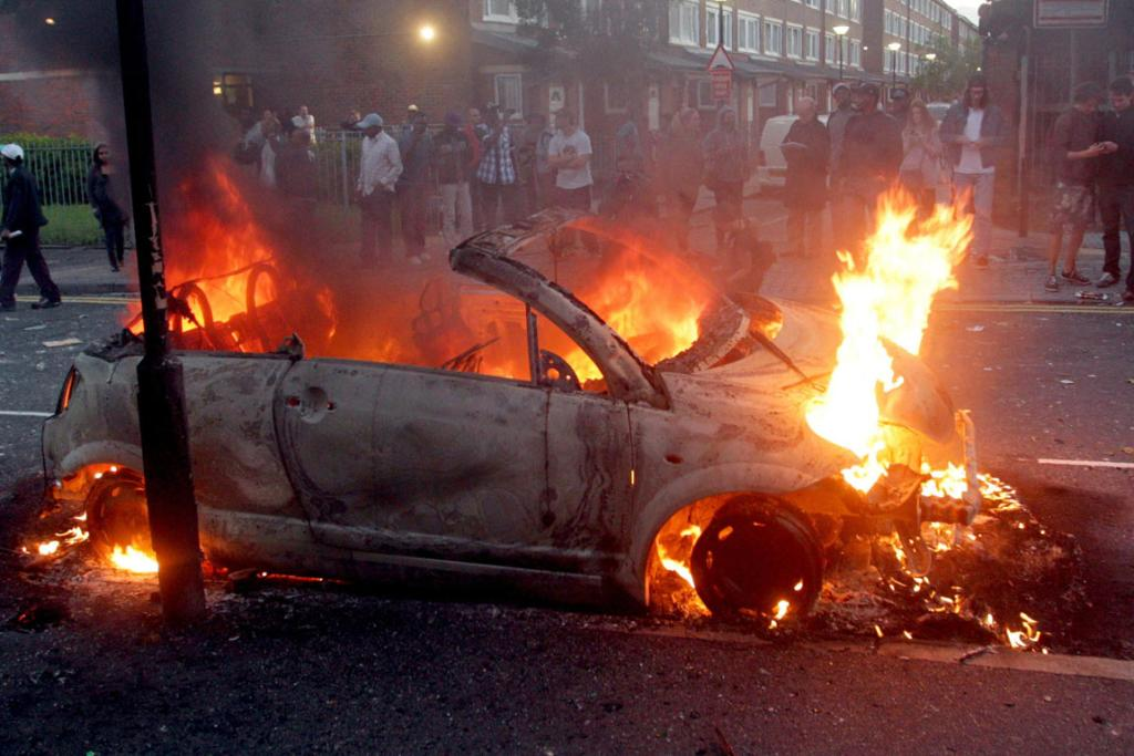 A car burns in Hackney, east London, as rioters rampage across London.