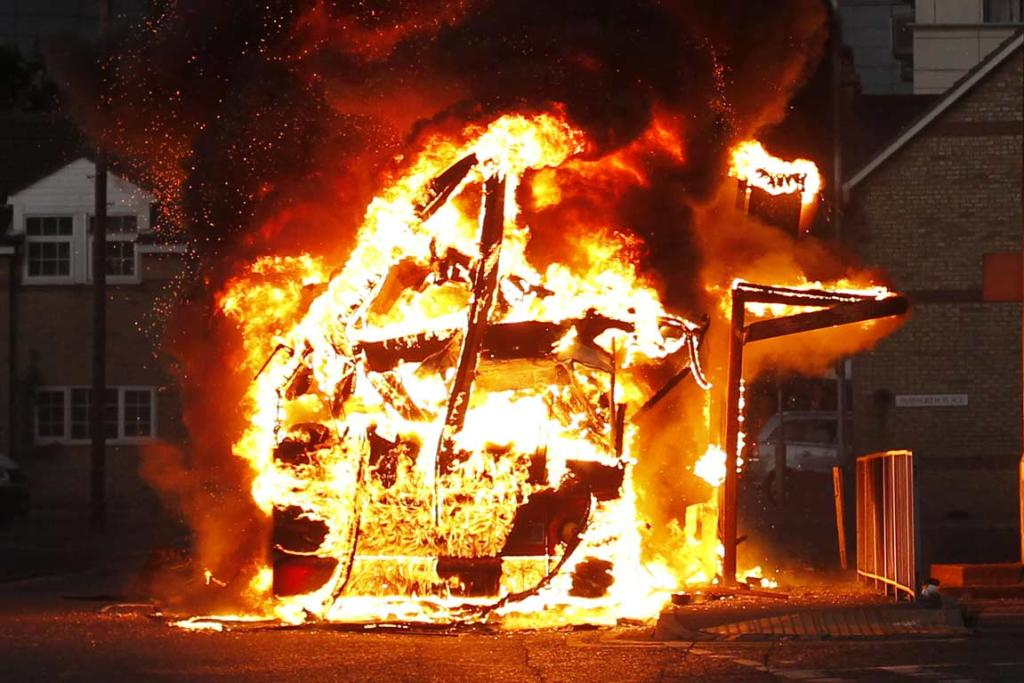 A bus is set on fire as rioters gathered in Croydon, south London.