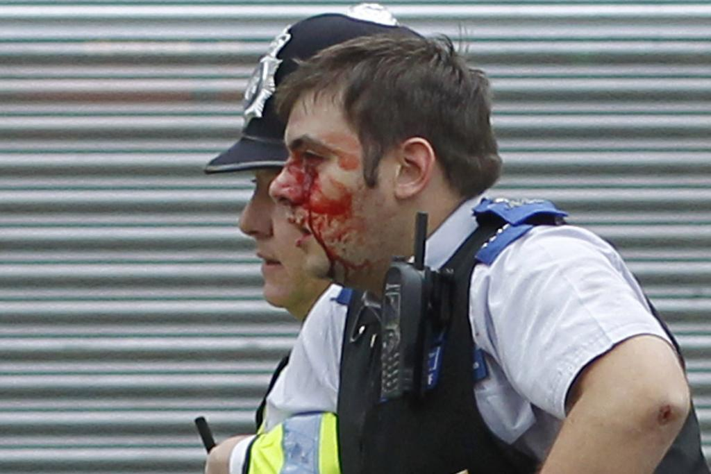 A police officer helps an injured officer from rioting in Croydon, south London.